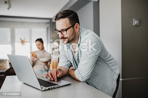 A young man is at home. He is using a laptop, young woman is in the background