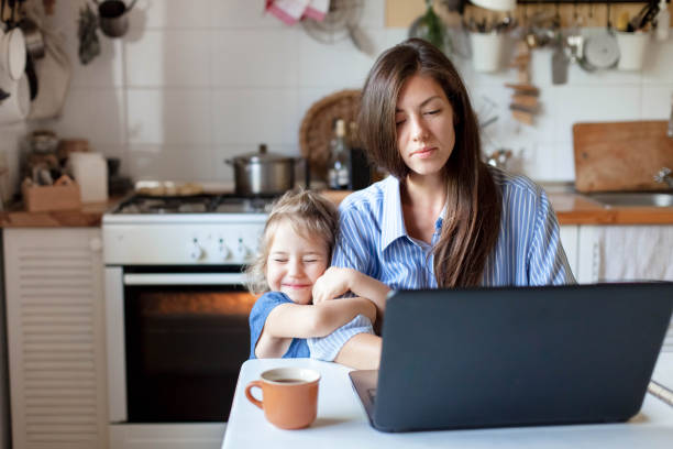 Working from home with kid. Happy daughter hugging mother. Young woman and cute child stock photo