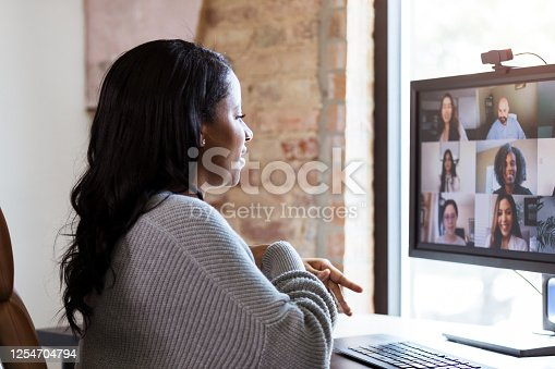 Since she has to work from home because of the coronavirus shutdown, the mid adult woman uses video conferencing to meet with her colleagues.