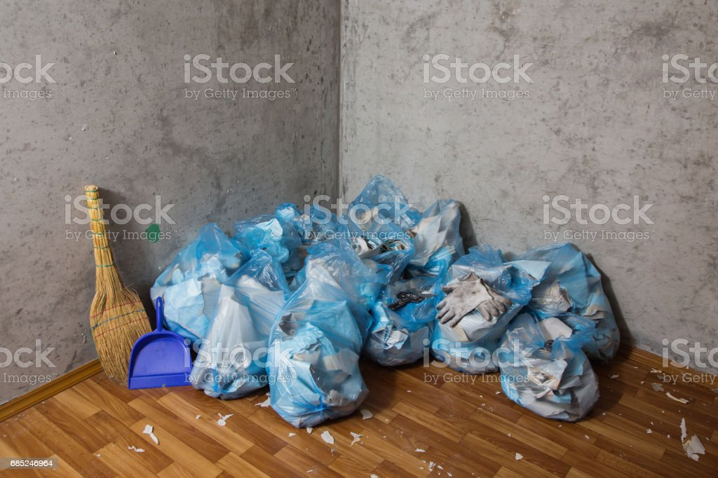 Working gloves, broom, dustpan. Collect garbage in the garbage bag, put things in order. Do makeovers. Putty knife lying on the floor foto de stock royalty-free