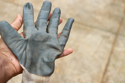 Working gloves held in hand after garden works with clean hands underneath. Protective gloves to safeguard hands on work process