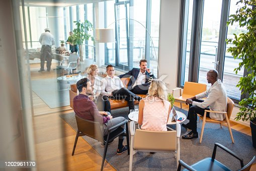Elevated personal perspective photographed through window of diverse business colleagues relaxing and talking in modern office lobby.