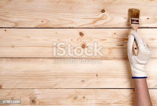 istock Working hand-in-glove keeping up brush on wooden background 479613495