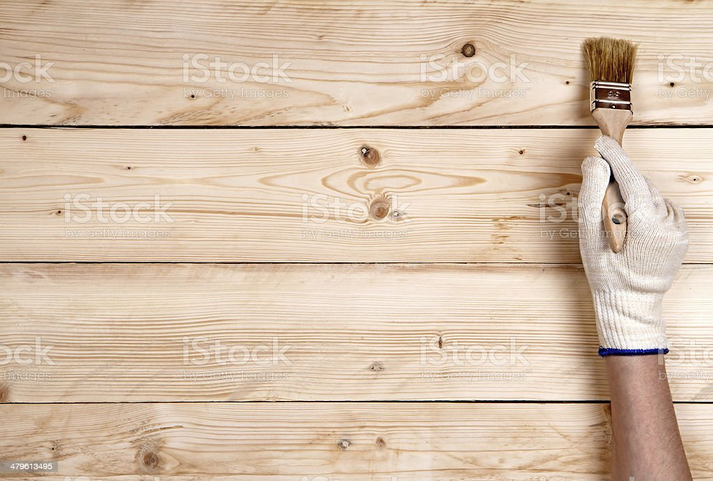 Working hand-in-glove keeping up brush on wooden background stock photo