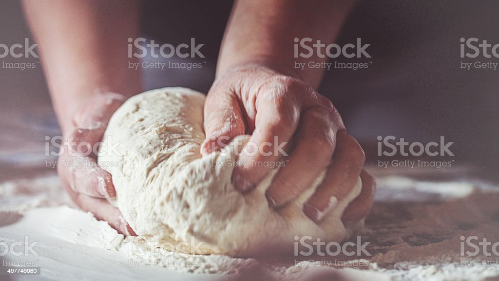 Working hands kneading bread dough stock photo