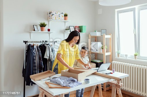 Indoor Shot of Beautiful Young Mother With Little Boy Working Together at Home and Preparing Package Product. SME Entrepreneur or Freelance Lifestyle Concept. Reconciliation of Family and Work-Life. Mid Adult Business Woman With Her Little Son in the Workplace. Working Mom.