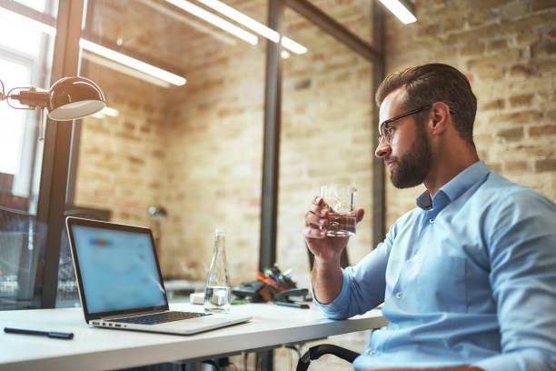 hart arbeiten. durstiger bärtiger geschäftsmann in brille und formeller kleidung trinken frisches wasser und blick auf laptop, während im modernen büro sitzen - leitungswasser trinken stock-fotos und bilder