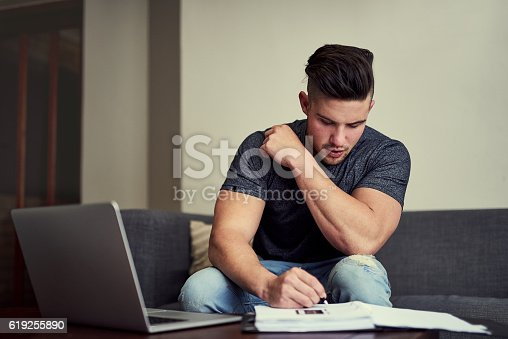 Shot of a driven young man using his laptop to work from home
