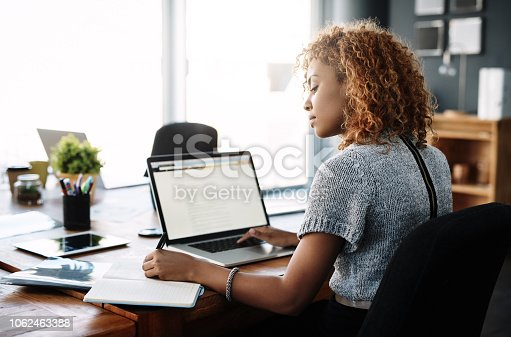 Shot of a young businesswoman working on a laptop in an office