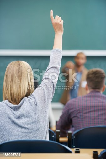 Rearview shot of a young woman raising her hand in a lecture hall