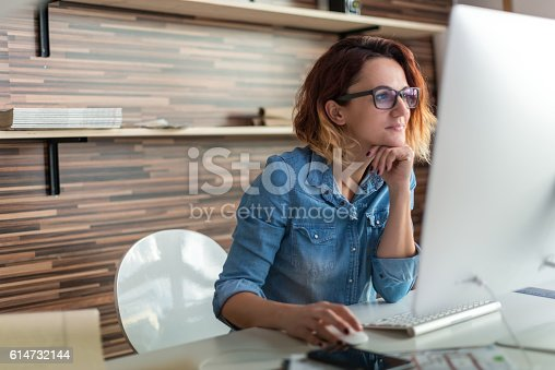 Businesswoman looking at a computer in an office.