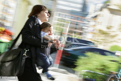 istock Working in a rush, mom carrying infant son outdoors 117144598