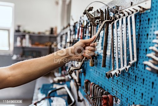 Photo of male mechanic reaching for Tools for Car arranged on the wall. Unrecognizable Person, a Caucasian male worker taking a tool from wall to repair a bicycle or car. Bike workshop interior. Young mechanic taking some tools in his shop. Motorcycle mechanic in his workshop taking a tool from his tool pane.