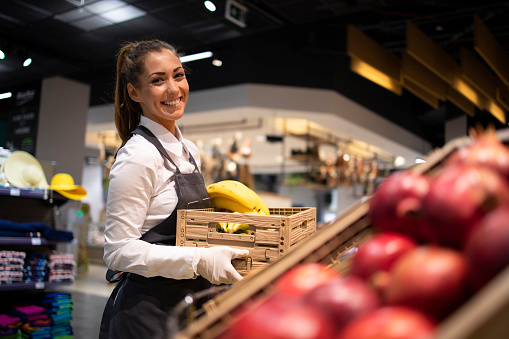 Working in grocery store. Supermarket worker supplying fruit department with food. Female worker holding crate with fruits.