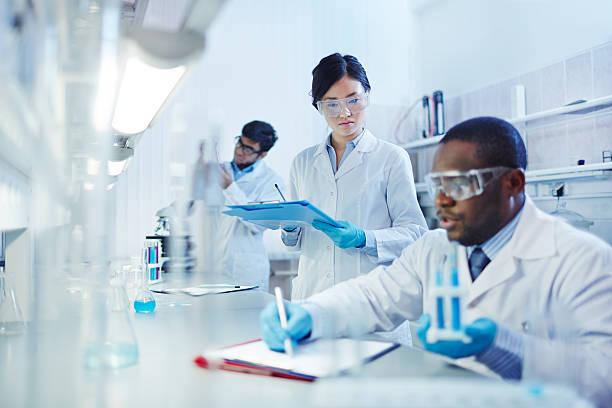 trabajando en laboratorio - biotecnología fotografías e imágenes de stock