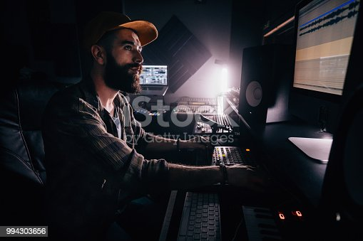 Hipster sound engineer working on audio control panel and producing music in professional music studio