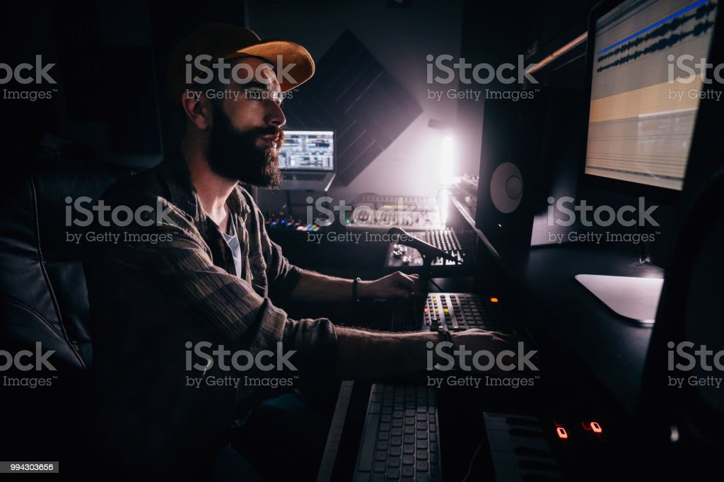 DJ working in music studio and looking at computer screen stock photo