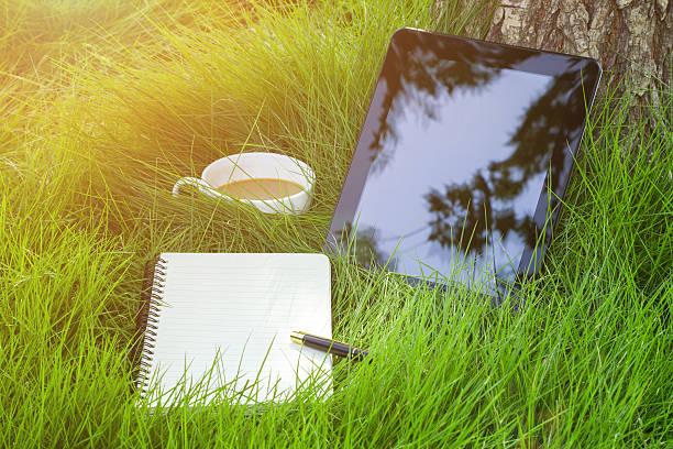 arbeiten in der natur: digital tablet und einen kaffee auf gras hintergrund - www kaffee oder tee stock-fotos und bilder