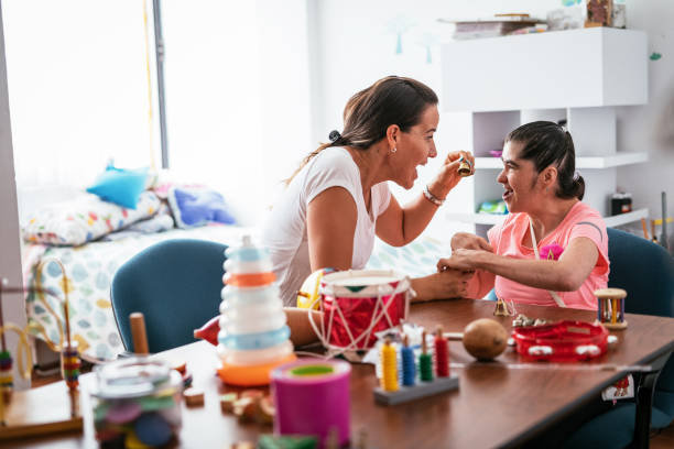 Working in nursery with person with Down Syndrome - foto stock