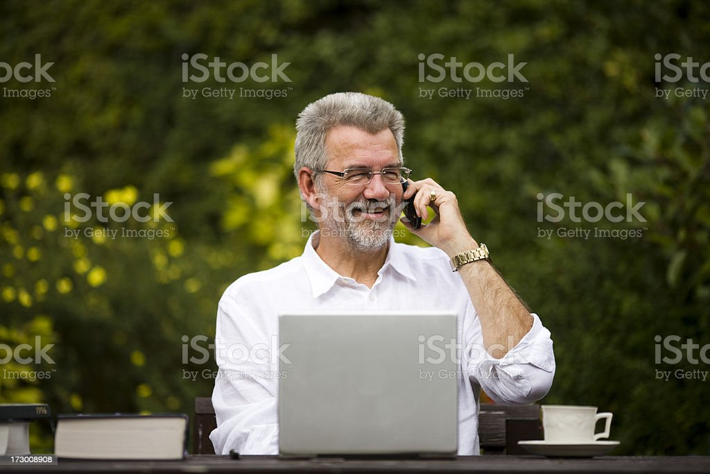 Working in the Garden Mature man using telephone & laptop in the garden Adult Stock Photo