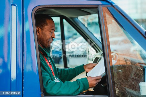 Senior manual worker is sitting in the driver's seat of his truck, working on some paperwork on a clipboard.