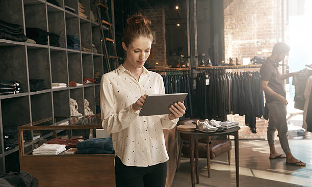 Working in-store and online Shot of a young shop owner working on a digital tablet with a customer in the backgroundhttp://195.154.178.81/DATA/istock_collage/a5/shoots/785349.jpg sales clerk stock pictures, royalty-free photos & images