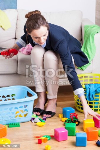 istock Working lady cleaning up toys 507510881