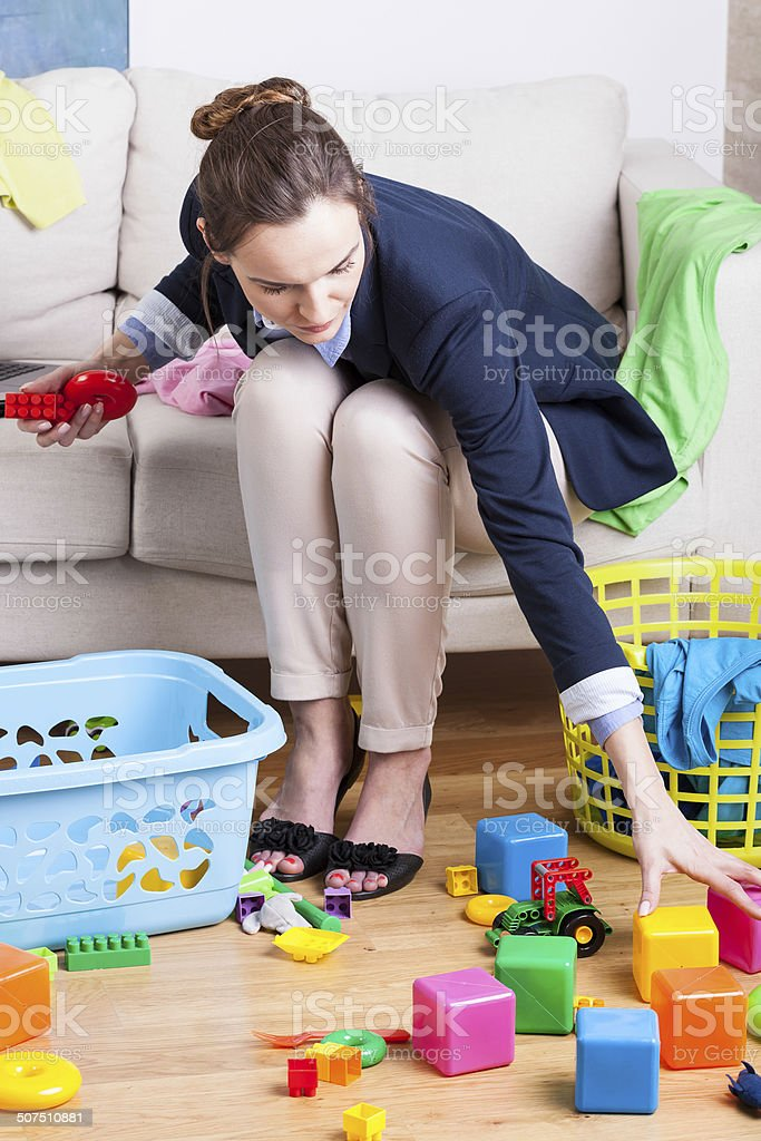 Working lady cleaning up toys stock photo