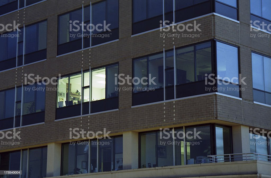 Working late, a single office building window is illuminated stock photo