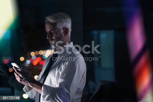 Shot of a businessman talking on the phone while working overtime at the office