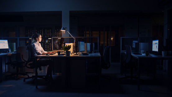 Working Late at Night in the Office: Businesswoman Uses Desktop Computer, Analyzing, Using Documents, Solving Problems, Finishing Important Project. Diligent Ambitious Young Worker. Side View
