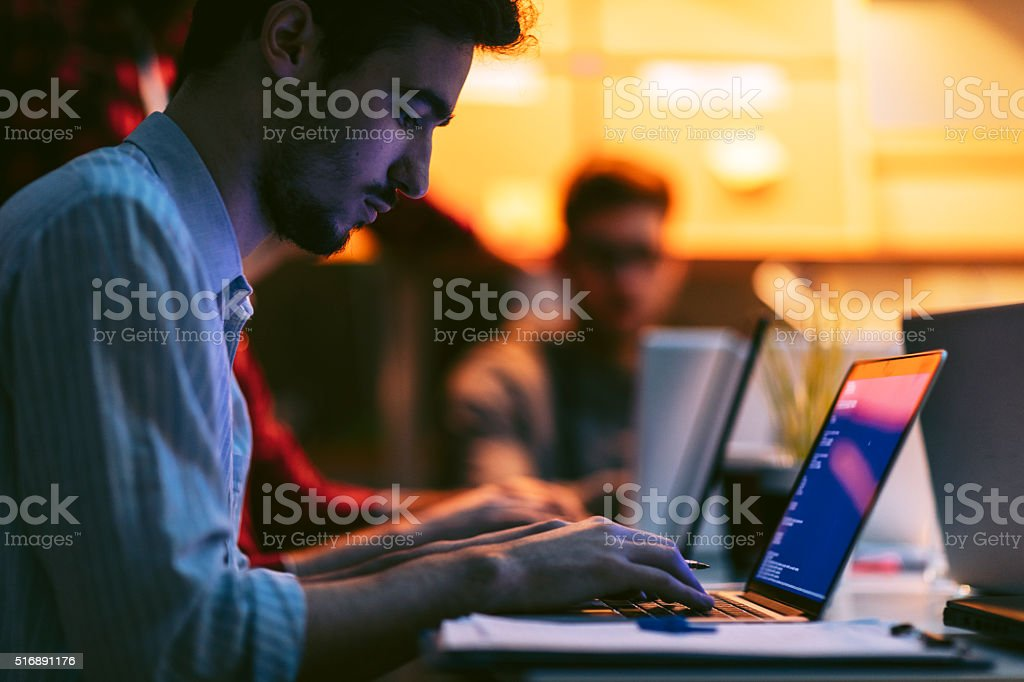 Male entrepreneur working late in office. He is sitting, using his...