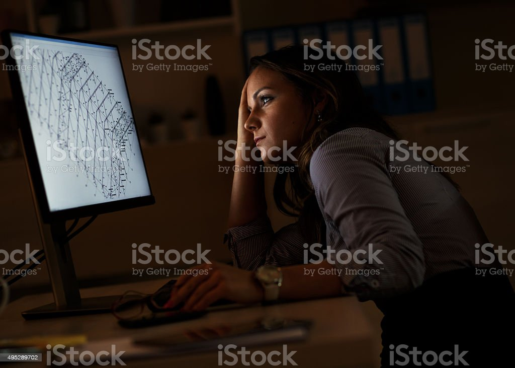 Working late Young female business woman working at home.She works late into the night looking at monitor. 2015 Stock Photo
