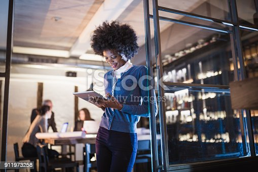 istock Working late. Young African-American woman architect using digital tablet in front of architecture studio. 911973258
