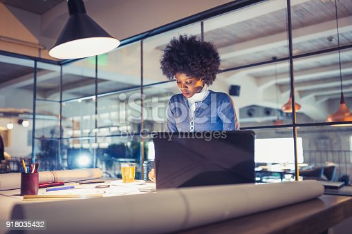 918035432 istock photo Working Late. Young African-American woman, architect working late in office 918035432