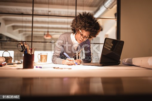 918035432 istock photo Working Late. Young African-American woman, architect working late in office 918035462