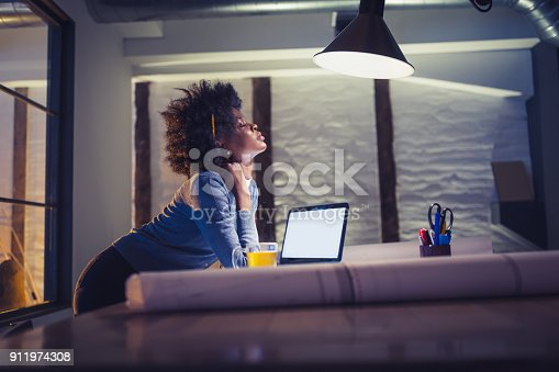 1012363738 istock photo Working late. Young African-American woman working in office 911974308