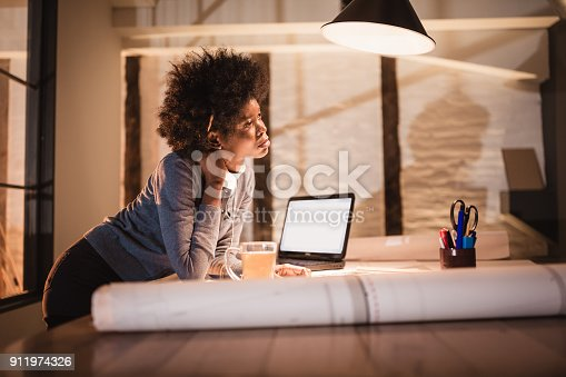 1012363738 istock photo Working late. Young African-American woman working in office 911974326