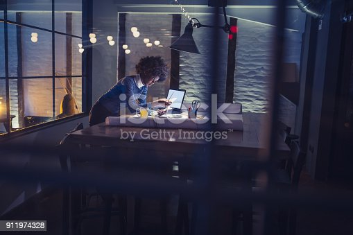 918035432 istock photo Working late. Young African-American woman working in office 911974328