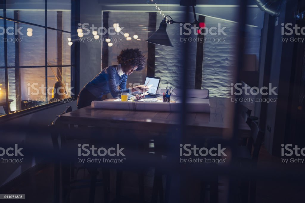 Working late. Young African-American woman working in office stock photo