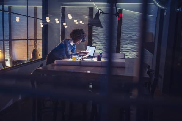 trabajo tarde. mujer joven afroestadounidense trabajando en oficina - trabajar hasta tarde fotografías e imágenes de stock
