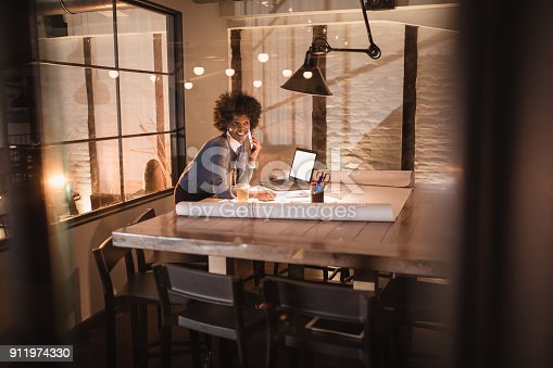918035432 istock photo Working late. Young African-American woman working in office 911974330