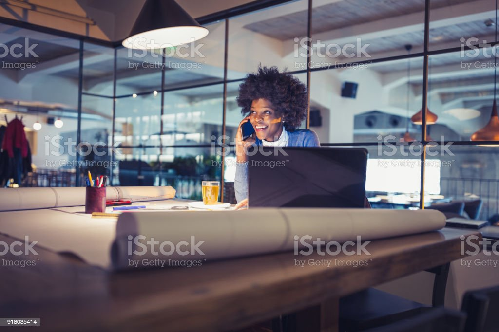 Working Late. Young woman, architect working late in office stock photo