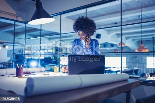918035432 istock photo Working Late. Young woman, architect working late in office 918035428