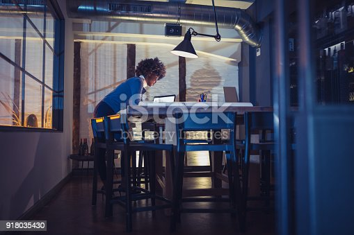 918035432 istock photo Working Late. Young woman, architect working late in office 918035430