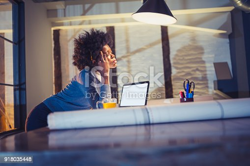918035432 istock photo Working Late. Young woman, architect working late in office 918035448
