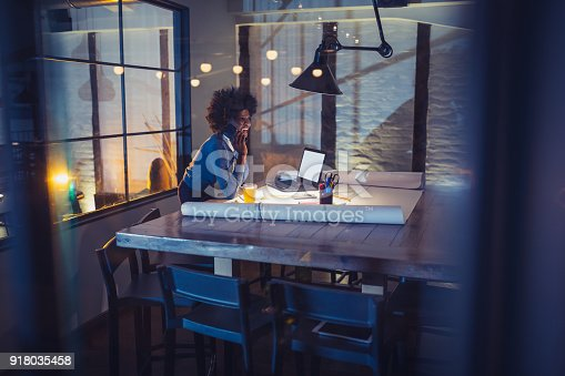 918035432 istock photo Working Late. Young woman, architect working late in office 918035458