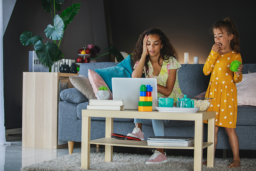 Wide shot of domestic living room where female exhausted entrepreneur sits on her couch while answering business e-mails on her computer with her little girl around.