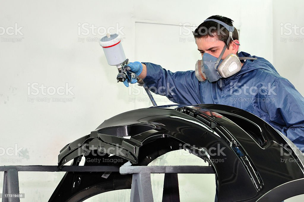 Working male painting part of a car in a paint booth stock photo