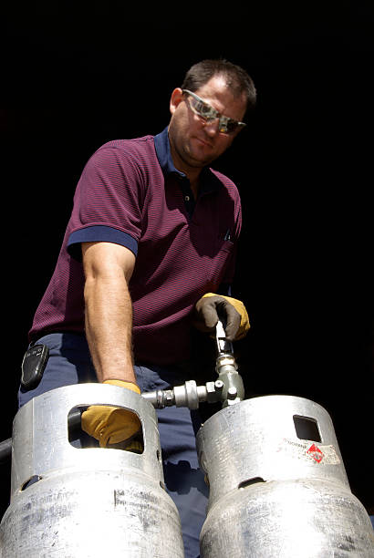 working man filling propane - mikefahl stock pictures, royalty-free photos & images